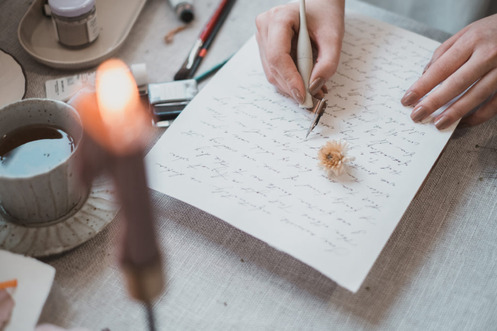 a calligrapher writing Wedding vows with candlelight