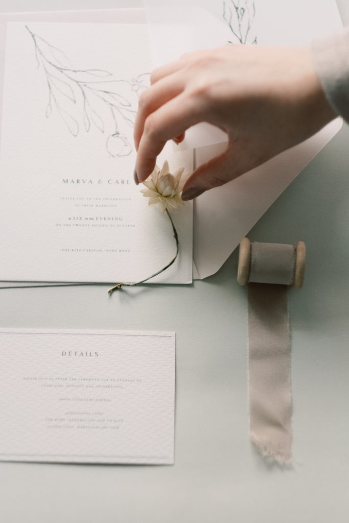 A Wedding Calligrapher styling wedding invitation on table