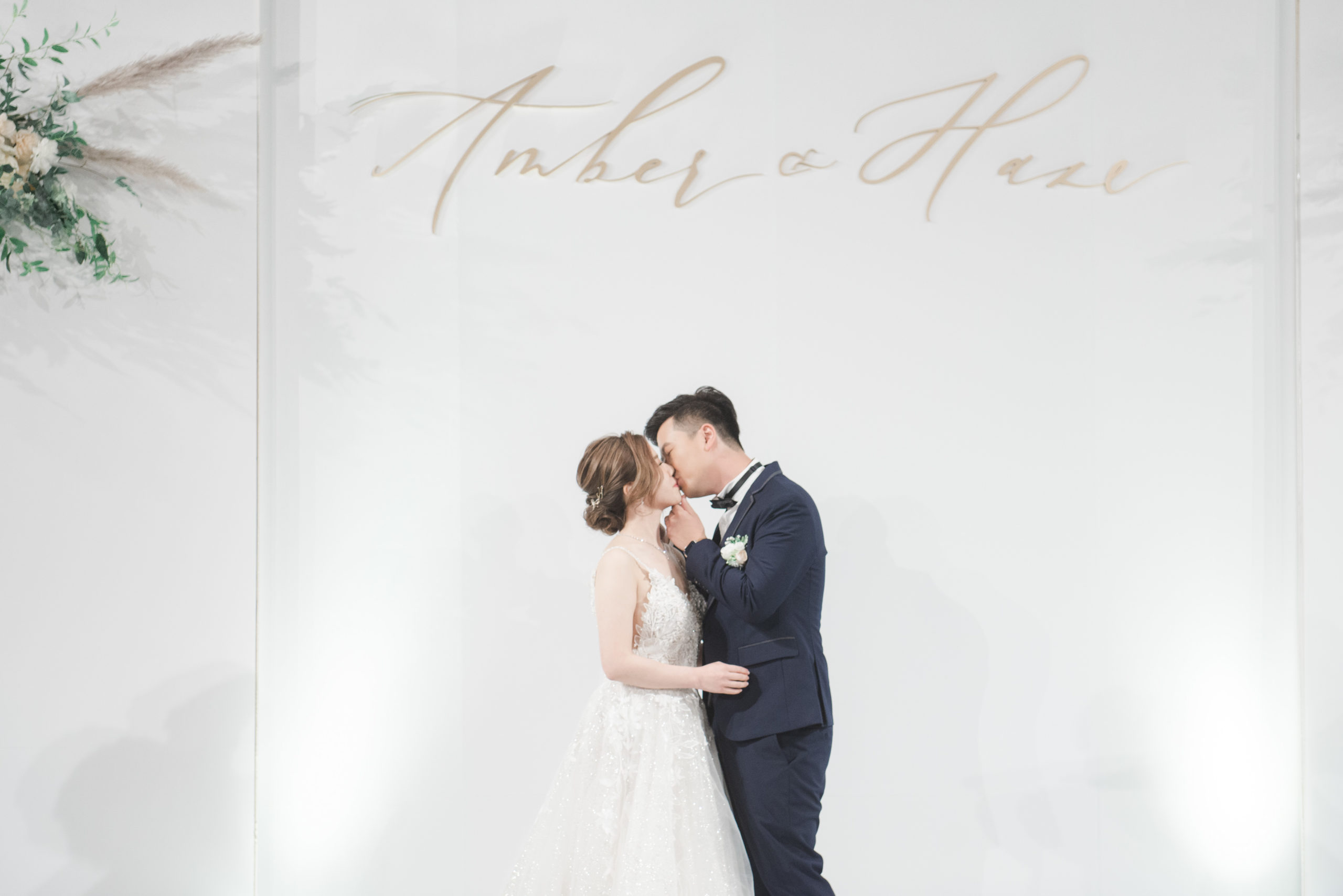 couple kissing in front of the calligraphy wedding backdrop