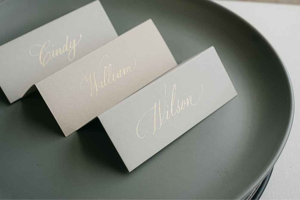 Folded place cards in gold copperplate calligraphy