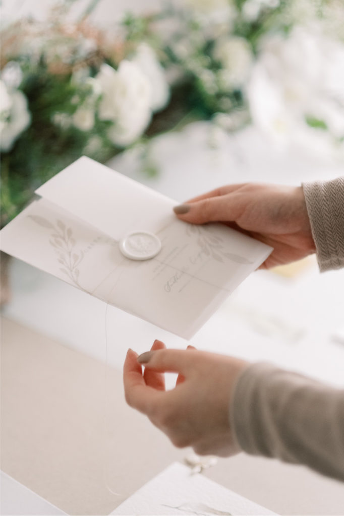 holding an wedding invitation with vellum wrap and waxseals with greenery floral
