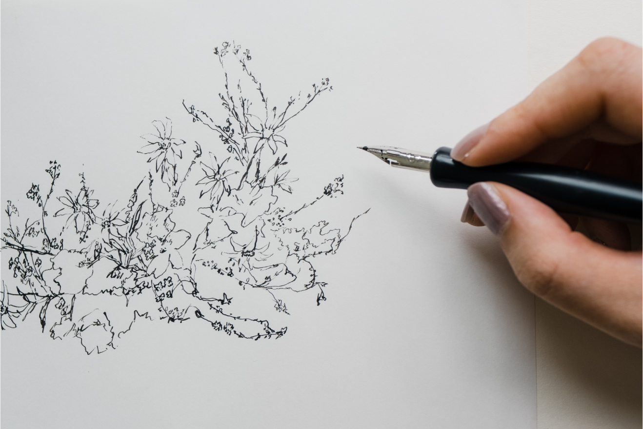 holding a dippen to draw floral ink sketches on paper